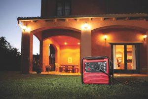 groupe électrogène rouge et maison éclairé