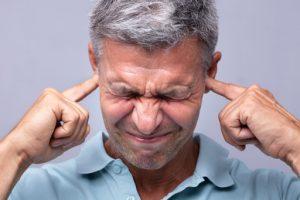 homme qui se bouche les oreilles